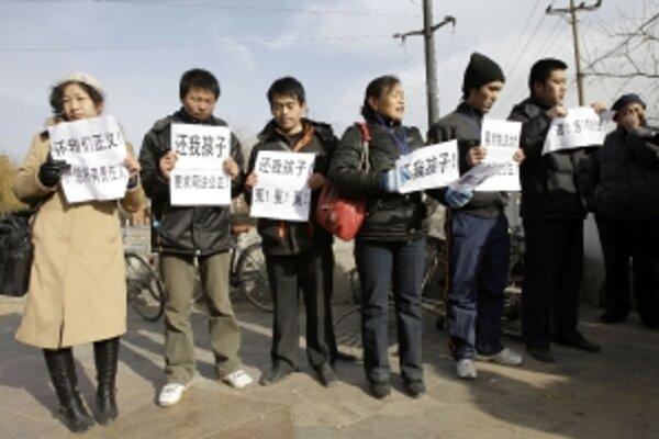 Príbuzní detí, ktoré zomreli na následky otravy melamínom, stoja s plagátmi pred budovou súdu.