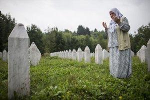 Bosnianska žena sa modlí vedľa truhly svojho príbuzného.