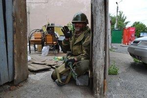 Proruský separatista zdraví fotografa, zatiaľ čo zaujíma svoju pozíciu počas ostreľovania ukrajinskými vládnymi jednotkami pri Sloviansku.