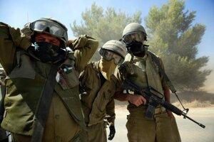 Izraelskí vojaci postupujú v Gaze, pred prachom sa chránia šatkami.