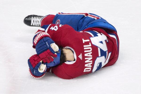 Hokejista Montrealu Canadiens Phillip Danault leží na ľade po tom, čo ho slovenský obranca v drese Bostonu Bruins Zdeno Chára nešťastne trafil strelou od modrej čiary do hlavy.