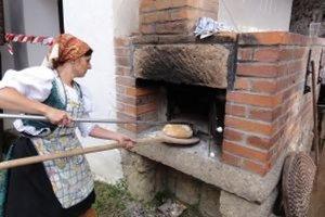 Chrumkavý chlieb je hotový, Jaroslava Caková ich z pece postupne vyberá.
