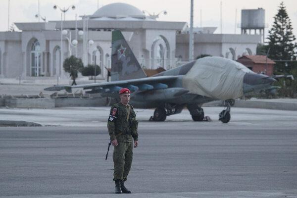 Ruský vojak a stíhačka Su-25 na leteckej základni Hemeimeem v Sýrii.