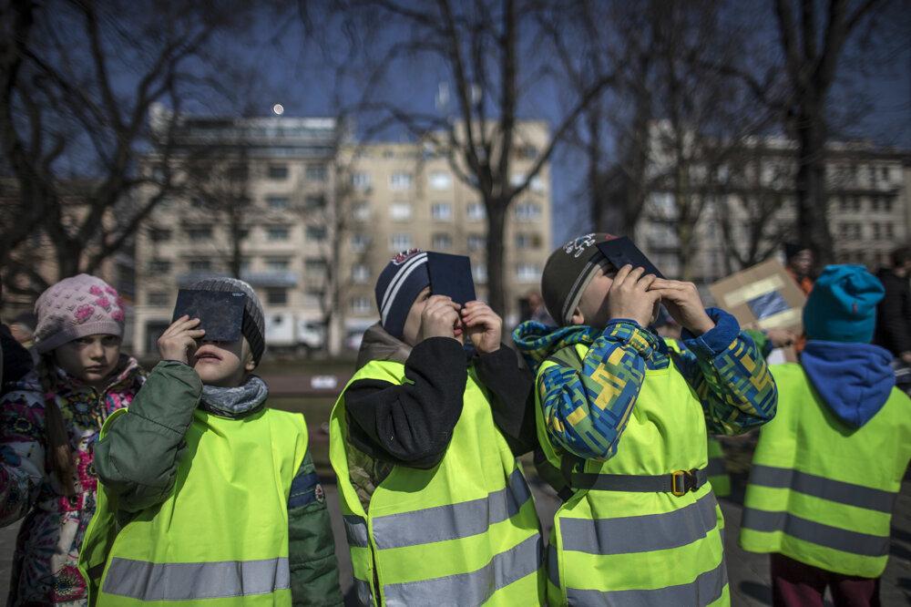 Deti znedaľekej školy pozorujú zatmenie Slnka na nábreží Dunaja.