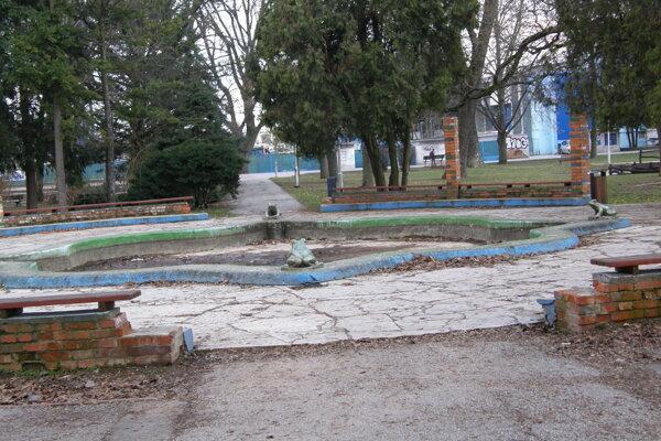 Žabia fontána v parku. Stoja len tri stĺpy zo stĺporadia, súčasťou ktorého sú lavičky.