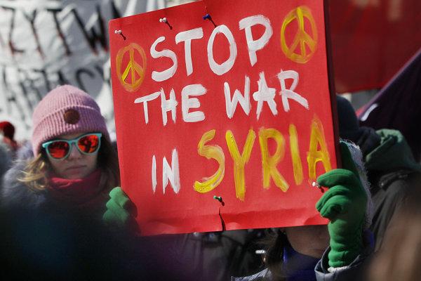 Ľudia niesli transparenty vyzývajúce na ukončenie konfliktov.