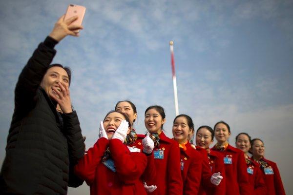 Ženy si robia selfie počas otváracej schôdze čínskeho Národného ľudového kongresu v Pekingu 5. marca 2018.