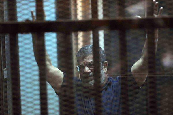 Zosadený egyptský prezident Muhammad Mursí zdvíha ruky v klietke pre obžalovaných na súde v Káhire 16. mája 2015.