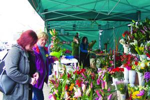 Tržnica opäť ožila kvetmi. V popredí pri predaji Jana Vidrová, vzadu viažu kvety Jana Marčeková a Eva Langsveldová.