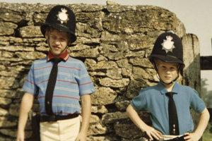 Na nedatovanej snímke z rodinného albumu pózujú princ  William (vľavo) a princ Harry v požičanej policajnej výstroji.