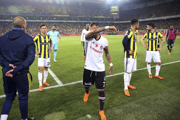 Hráči Besiktasu (uprostred) a Fenerbahce odchádzajú z trávnika v semifinálovom zápase Tureckého pohára.