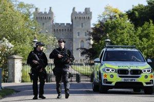 Ozbrojení policajti hliadkujú pred Windsorským zámkom.