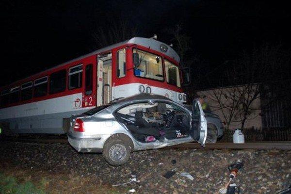 Auto zostalo zakliesnené pod vlakom.