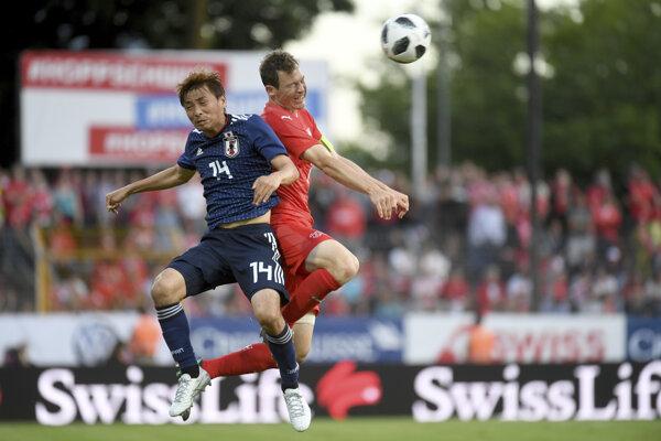 Stephan Lichtsteiner (vpravo) zvádza hlavičkový súboj s Japoncom Takashim Inuim.