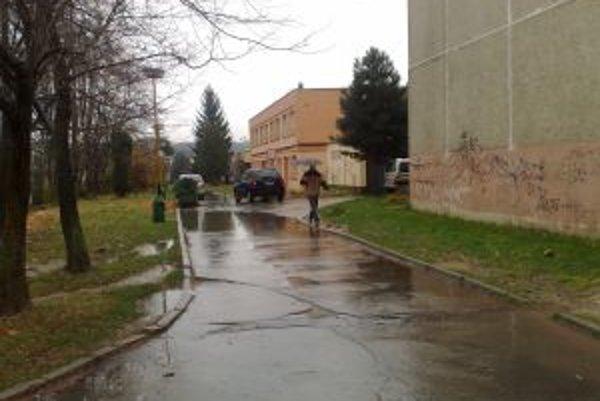 Bajzova ulica na Hlinách. Prepadnutú vozovku zaplavuje voda.