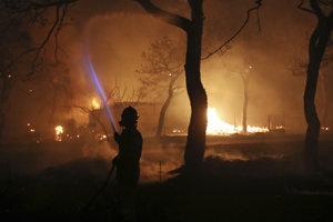Hasič bojuje s požiarom v blízkosti Atén.