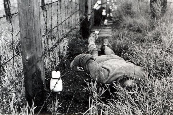Na fotografii z r. 1984 je telo muža, ktorý zahynul pri plote s vysokým napätím pri pokuse o prekročenie hranice s Rakúskom na úseku Bratislava - Devín.