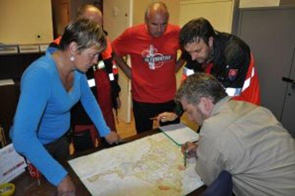 Policajti s členmi ORS a Zuzaninou mamou nad mapou Piľska.