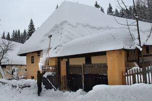 Zhadzovaním snehu zamestnanci skanzenu chránia strechy dreveníc pred preborením.