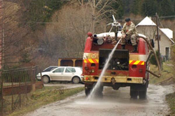 """Po zemných strojoch nastúpila do práce """"hasička"""" - hasičská cisterna so striekačkou a malým vodným delom."""