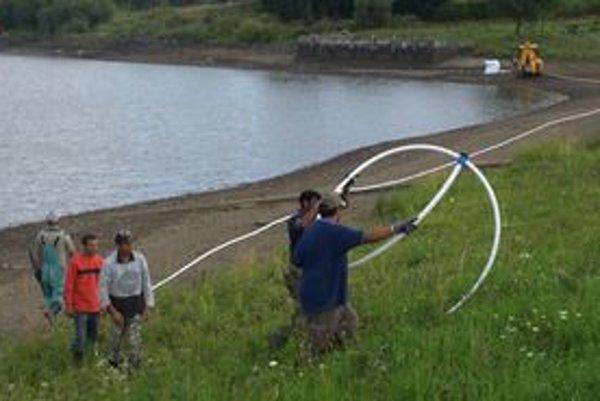 Jedna partia ukladá káble po brehu vyrovnávačky, druhá popod vodu.