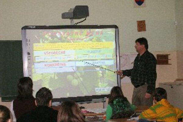 Riaditeľ Dzurko používa interaktívnu tabuľu na hodinách slovenčiny.