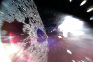 Záber zachytil Rover-1A počas poskakovania po Ryugu. Vľavo je povrch asteroidu, svetlá škvrna vpravo vznikla kvôli Slnku.