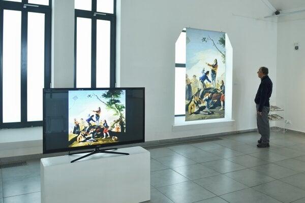 Na snímke muž si prezerá jednu z reprodukcií obrazu počas výstavy Francisco Goya Vízie.