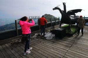 Ľudia si odnášajú na pamiatku fotografiu s drakom Demianom.