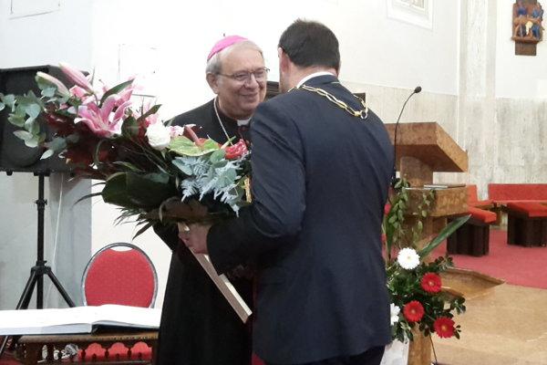 Arcibiskup preberá ocenenie z rúk primátora Kleina.