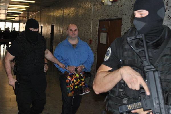 Braňa Adamča priviedla na súd štvorčlenná eskorta. Putá mal na rukách i nohách.