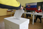 Voliči vhadzuje obálku s hlasovacími lístkami do volebnej schránky v Púchove.
