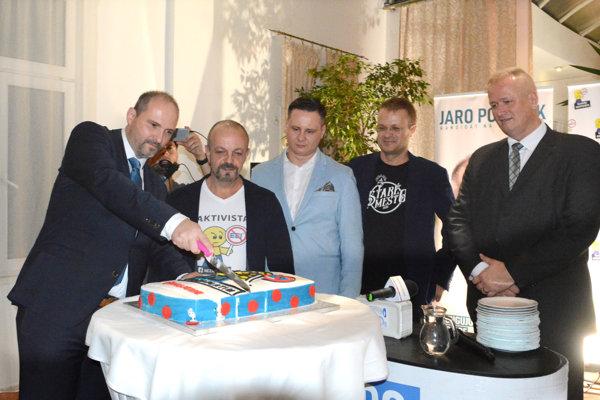 Jaroslav Polaček (vľavo) krája víťaznú tortu.