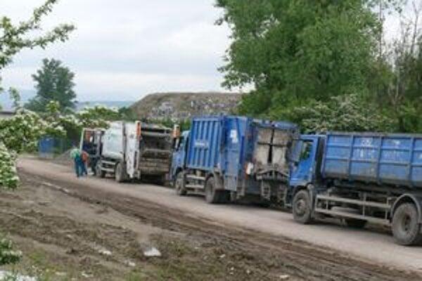 Po komplikovanom príjazde cez poľnú cestu stoja autá pred skládkou a čakajú na vysypanie odpadu.