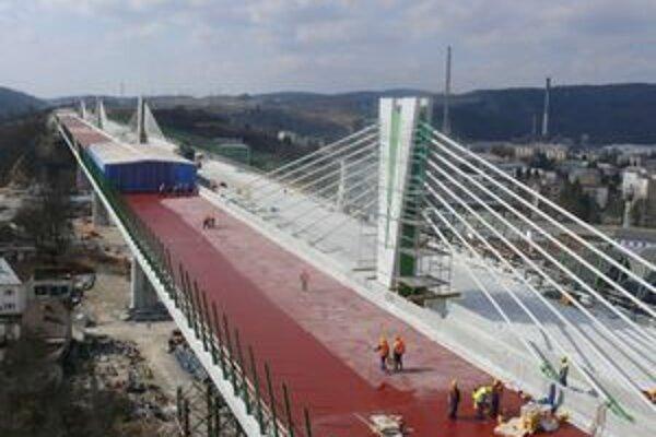 Na vozovke je červená pečatiaca vrstva, osadené sú konštrukcie na protihlukové steny. Stavbári natierajú pylóny aj piliere.