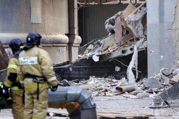 Pracovníci ruského ministerstva pre mimoriadne situácie sa pozerajú na trosky pred poškodeným bytovým domom v meste Magnitogorsk.
