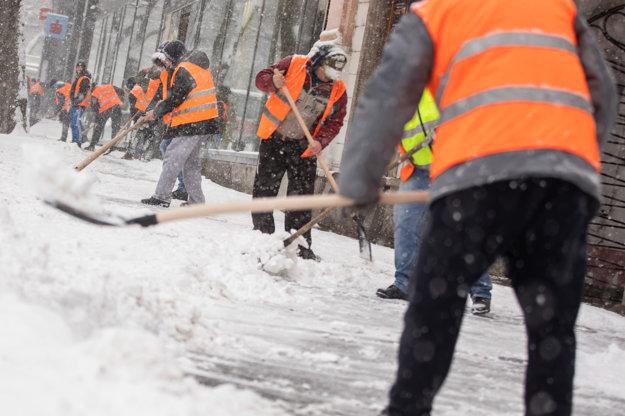 Odsúdení vo výkone trestu z Ústavu na výkon trestu odňatia slobody v Justičnom paláci pomáhajú s odpratávaním snehu na námestí SNP.
