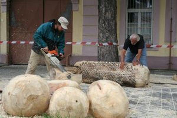 Umelci s motorovou pílou tvoria svoje diela z dreva na námestí neďaleko fontány. Vľavo Michal Hanula z Ružomberka, vpravo  Stephen Holm z USA.