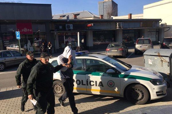 Obvinený v sprievode polície.
