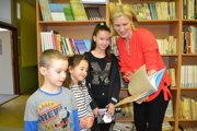 Učiteľka Anna Daňová so žiakmi, ktorí darovali  do školskej knižnice knihu.