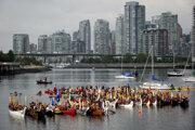 Kanadskí Indiáni vo Vancouveri počas týždňa zmierenia zdravia divákov zdvihnutými pádlami.