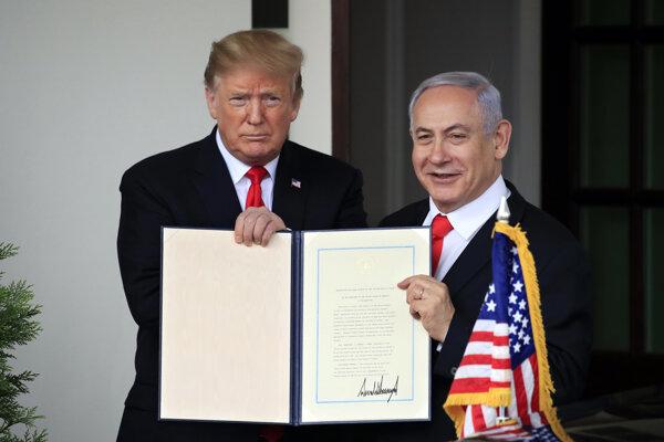 Americký prezident Donald Trump a vpravo izraelský premiér Benjamin Nehanjahu držia spoločne dekrét o uznaní suverenity Izraela nad Golanskými výšinami v Bielom dome vo Washingtone.