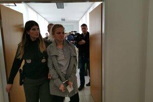Alexandra prichádza do pojednávacej miestnosti.