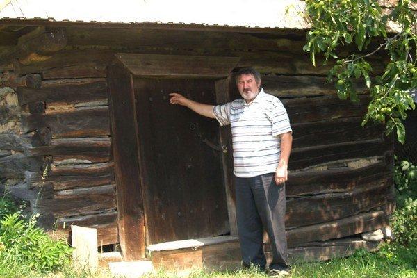 Starosta Ján Karman pred vyše dvestoročnou stavbou, ktorá pripomína malú drevenicu.