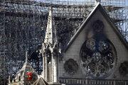 Hasič kráča po balkóne Katedrály Notre-Dame v Paríži.