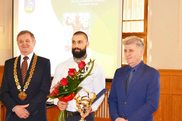 Najúspešnejším športovcom Nitrianskeho kraja za rok 2018 je naturálny kulturista Erik Tóth zo Šale. Vľavo predseda NSK Milan Belica, vpravo vedúci odboru kultúry a športu Úradu NSK Ľubomír Kleštinec.
