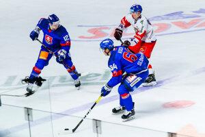 Hosťujúci Lukáš Rousek napáda slovenských hokejistov.