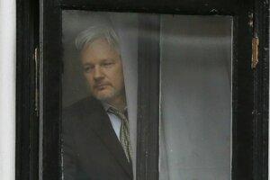 Julian Assange sa pozerá z okna ekvádorskej ambasády v Londýne.