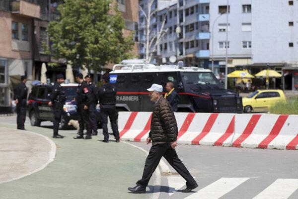 Muž kráča okolo talianskych karabinierov mierovej misie pod vedením NATO v Kosove (KFOR), ktorí strážia hlavný most v  etnicky rozdelenom meste Mitrovica ležiacom na severe Kosova.