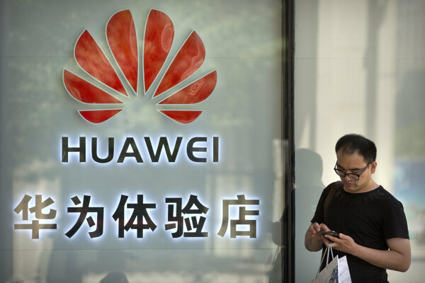 Muž pred predajňou Huawei v Pekingu.